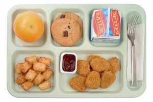 A straight shot of a tray of a typical schooll unch tray consisting of chicken nuggets, tater tots, an orange, cookies and milk.